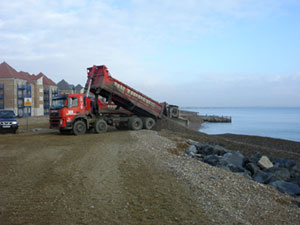 Shingle that collects against the south harbour arm has to be transferred around the harbour.